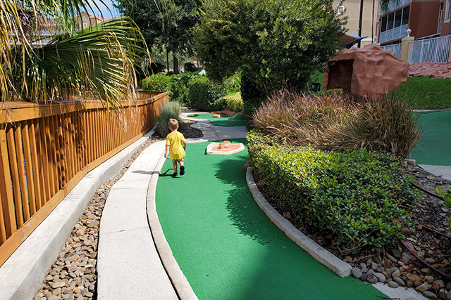 Little boy on green while playing miniature golf