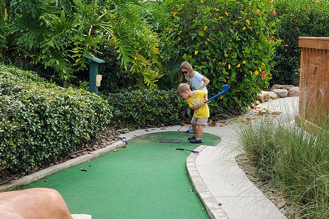 2 little kids playing miniature golf