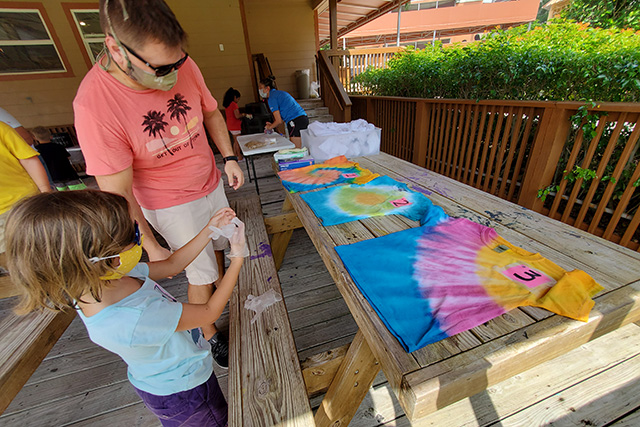 Little girl putting on gloves to make a tie dye shirt