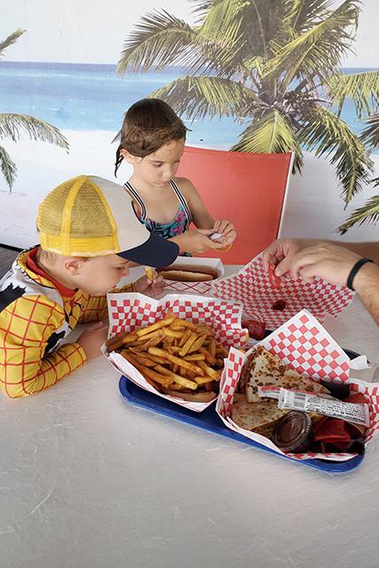Kids eating hot dog and fries at a resort