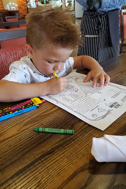 Little boy coloring in on restaurant kids menu