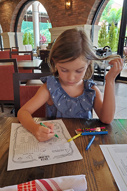 Little girl coloring in on restaurant kids menu