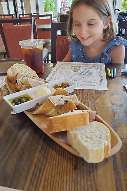 little girl looking at a large platter of bread with array of butter and dips