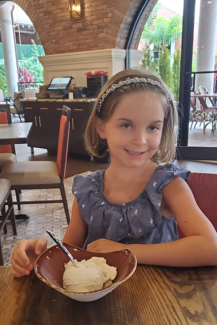 little girl wearing a blue dress with a bowl of gelato at an Italian restaurant