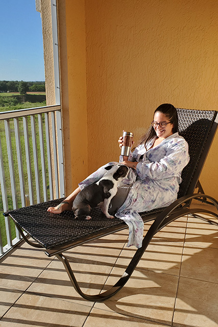 Woman wearing a floral robe drinking coffee with a Boston Terrier sitting next to her on the lounge chair