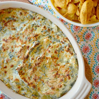 Baked Cheesy Spinach Artichoke Dip next to a bowl of corn chips for dipping