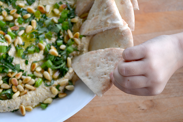 hand picking piece of pita from bowl of homemade hummus