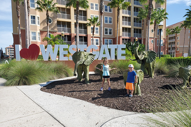 2 kids standing in front of elephant states and I love Westgate sign at resort