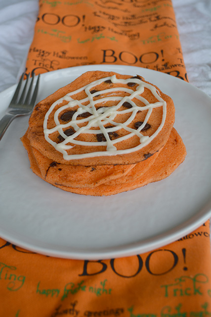 Orange Chocolate Chip Pancakes with a spider web design on top with cream cheese frosting on a white plate with a halloween themed napkin