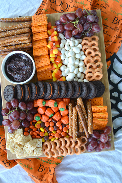 Halloween Themed Dessert Charcuterie Style Board with candy corn, grapes, dessert hummus, pretzels, mini candy pumpkins, and more