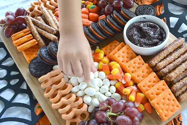 child's hand grabbing a yogurt raisin from Halloween Themed Dessert Charcuterie Style Board