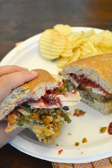 hand holding a Pilgrim Sandwich revealing the Thanksgiving leftovers inside