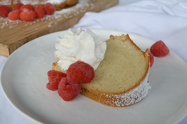 Slice of pound cake on a white plate topped with fresh raspberries and whipped cream