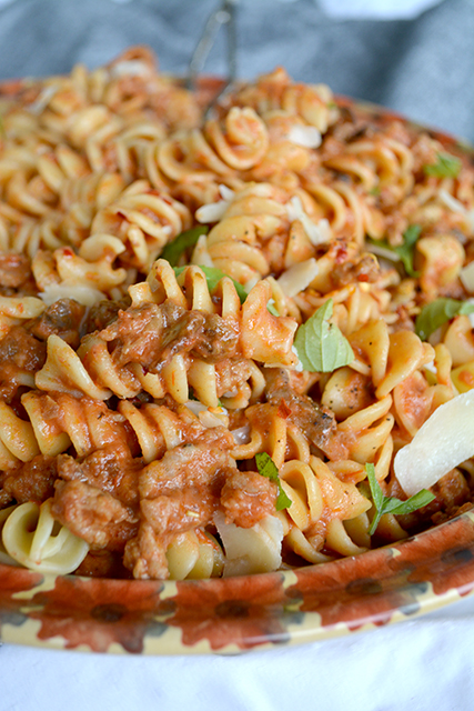 close up of hearty mushroom and sausage pasta in a large serving bowl topped wth ripped basil and parmesan cheese