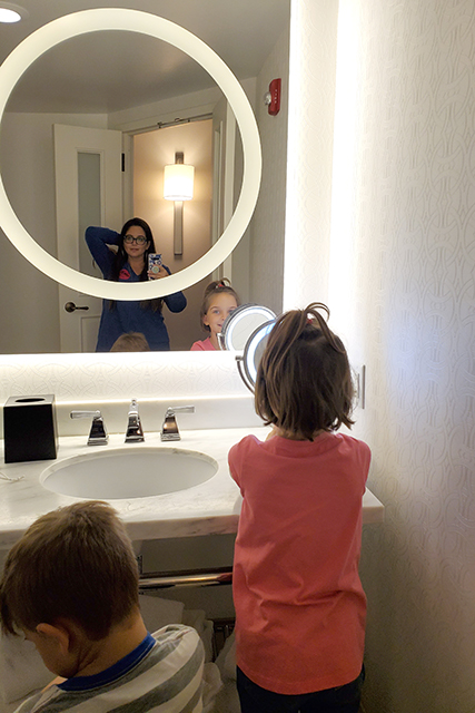 bathroom selfie at hotel room mirror with women and kids in picture