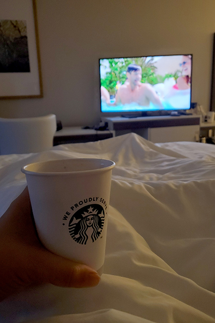 drinking coffee and watching TV in a hotel bed