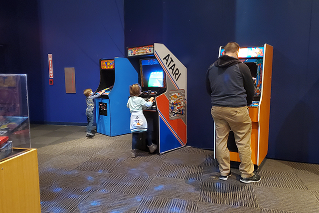family playing arcade games at MOSH exhibit
