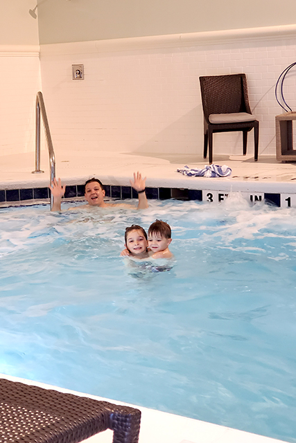 family swimming in indoor pool at hotel