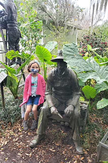 little girl sitting new to statue of field worker at Leu Gardens