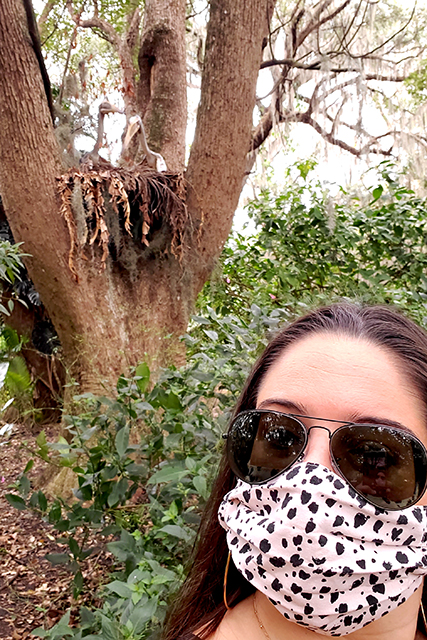 woman took selfie style picture wearing sunglasses and wearing a mask in front of a tree
