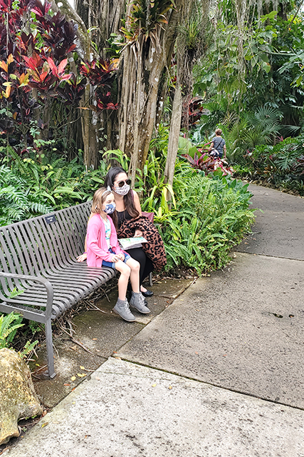 woman and little girl sitting on a bench looking off into the distance