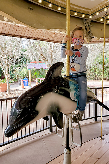 little girl on a carousel at Jacksonville Zoo