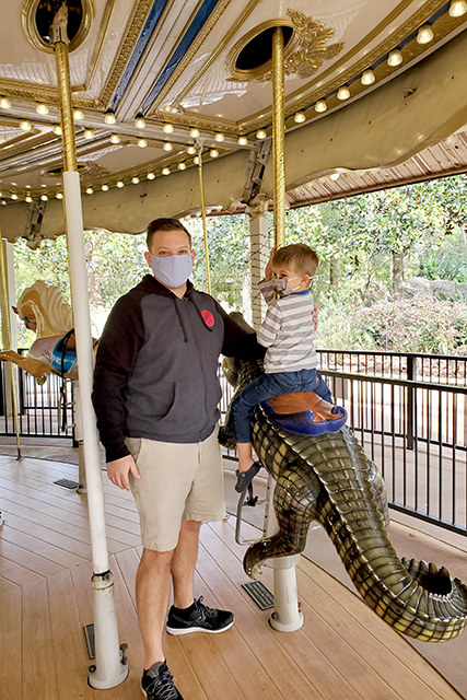 father standing new to little boy on the carousel at Jacksonville Zoo
