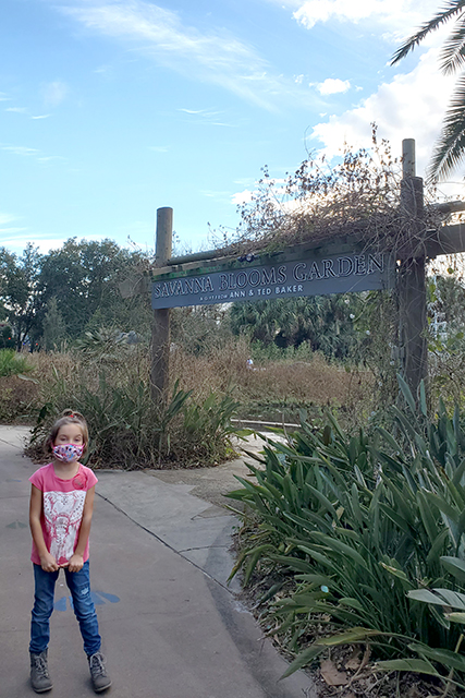 girl standing in front of Savana Blooms Garden at Jacksonville Zoo