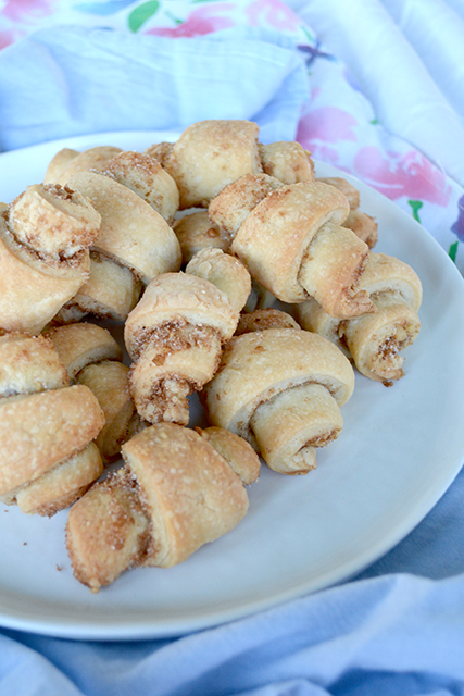pile of brown sugar and walnut rugelach cookies on white plate on blue and soft floral napkins