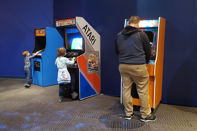 family playing on old arcade games in museum exhibit on toys
