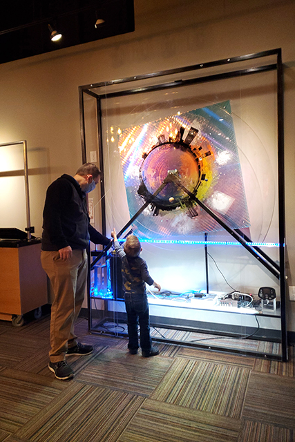 Man and small boy playing with digit art display at Jacksonville MOSH