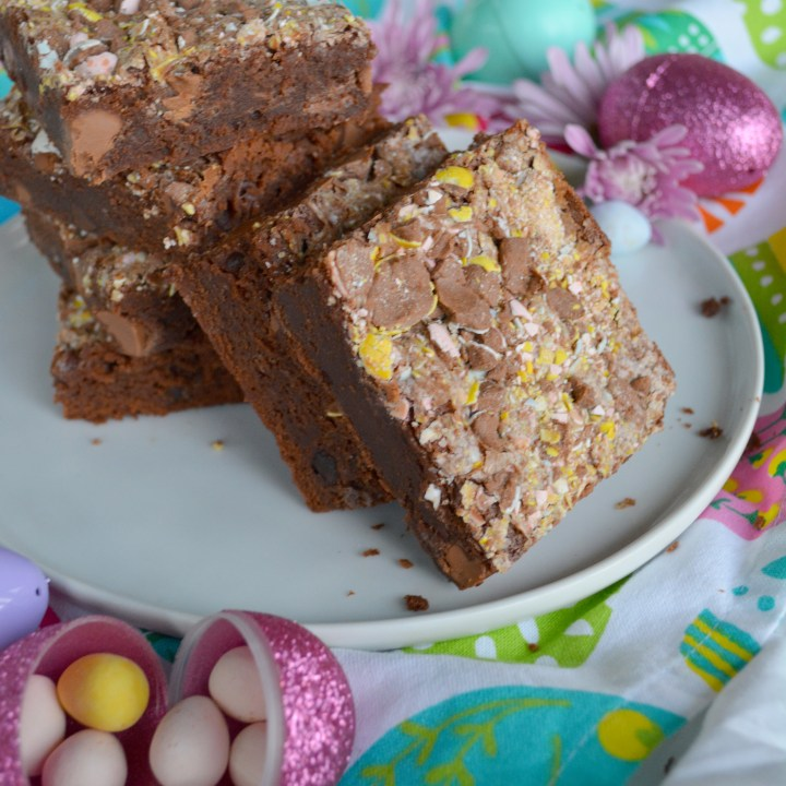 white plate with large Cadbury Mini Egg Brownies on it with candy, plastic Easter eggs, and flowers around it