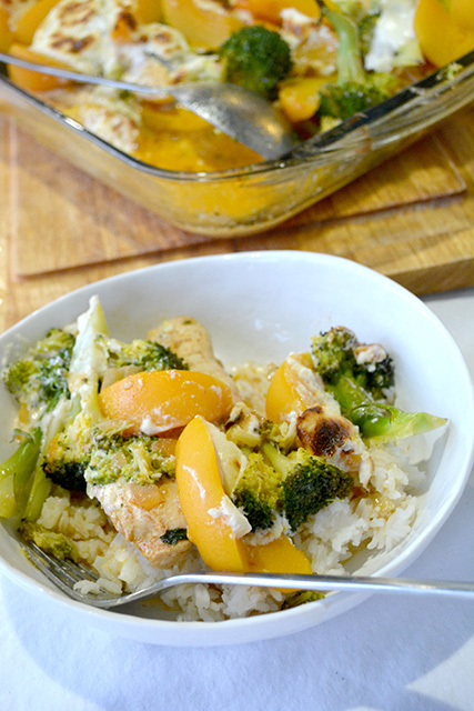 Chicken Broccoli Peach Bake served on rice in a white bowl in front of a pan of the casserole