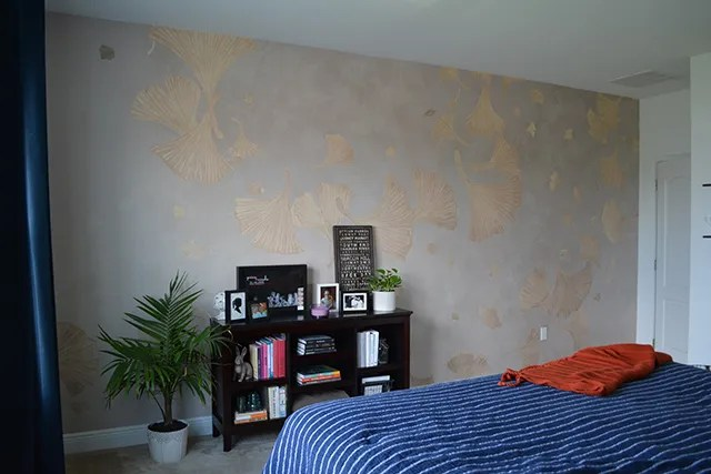 Large print ginkgo wallpaper to accent bedroom with dark wooden bookcase in front of it with plant next to it.