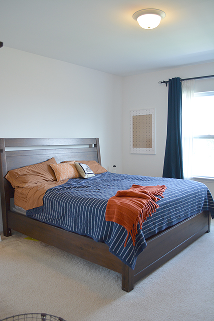 view of king sized bed with a blue and white stripped quilt with a orange throw on top.