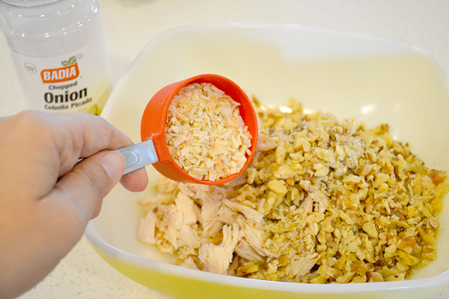 Pouring chopped dried onion from measuring cup into bowl of shredded chicken.