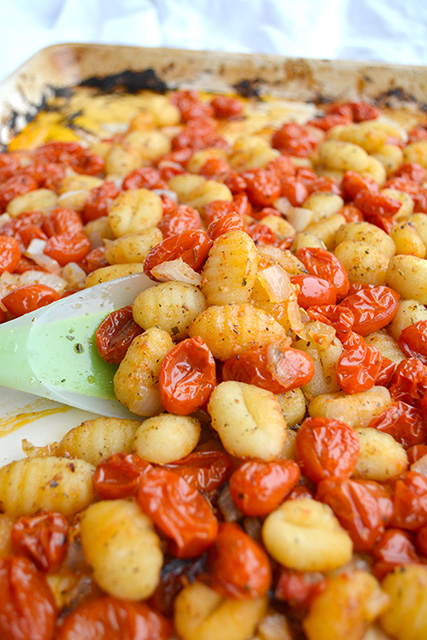 Rubber spatula lifting gnocchi and fresh tomato sauce up on sheet pan the dinner was made on.