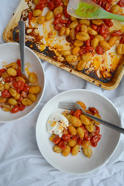 Overhead view of sheet pan dinner with fresh tomato sauce and potato gnocchi with bowls of pasta next to sheet pan.