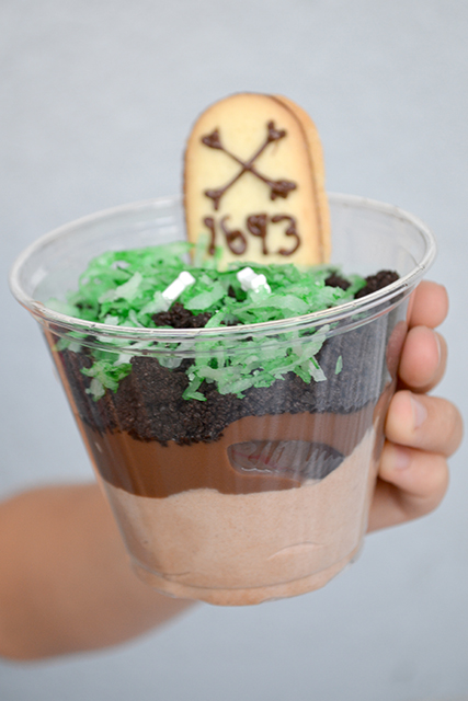 Child's hand holding layered chocolate pudding cup with cookie gravestone.