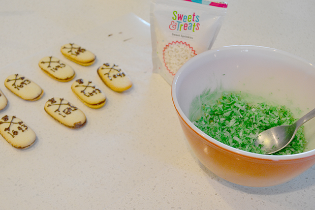 Bowl of shredded coconut dyed green next to decorated cookies.