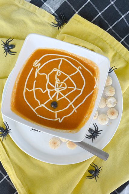 Overhead shot of Spider Web Soup accented with fake spiders around bowl.