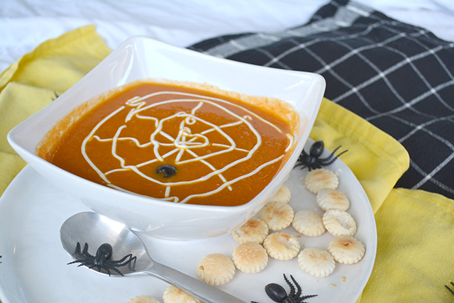 Fake spider sitting on spoon next to Tomato Pumpkin Soup that is topped with a sour cream spider web.
