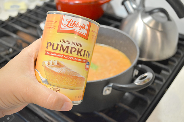 Hand holding can of pumpkin puree in front of pot of tomato soup.