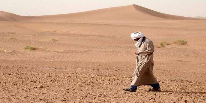 رجل يسير في الصحراء