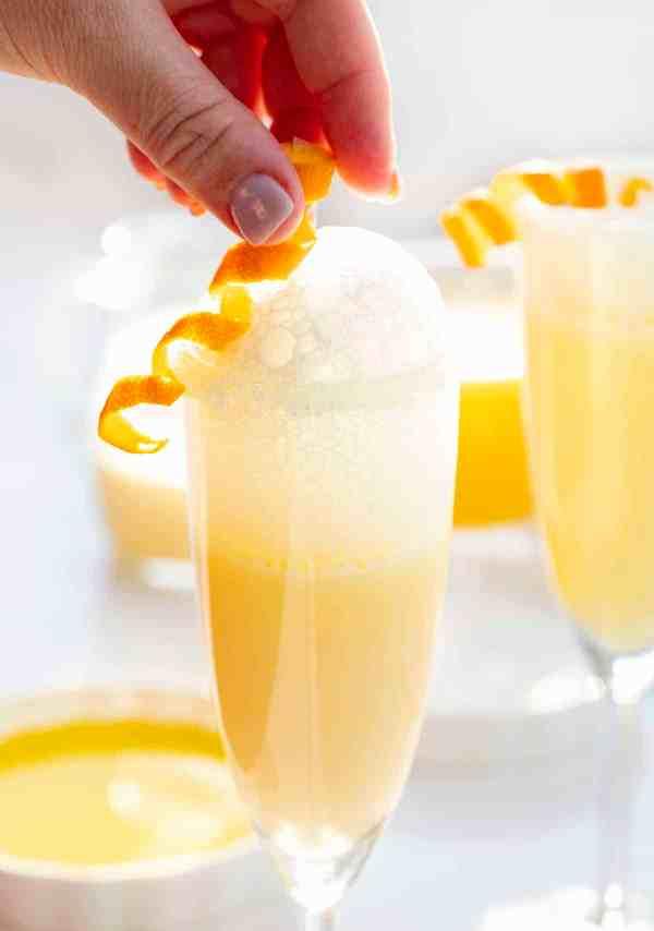 Placing spiraled orange peel garnish on top of creamsicle Prosecco