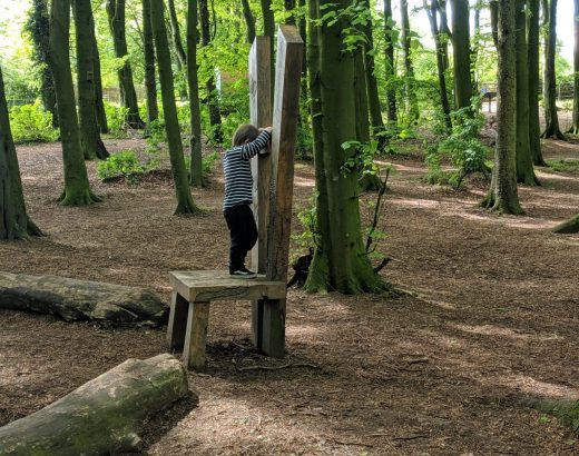 little boy balancing on the giant chair in the woods at hardwick park sedgefield