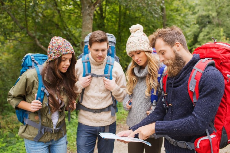 group-of-smiling-friends-with-backpacks-hiking