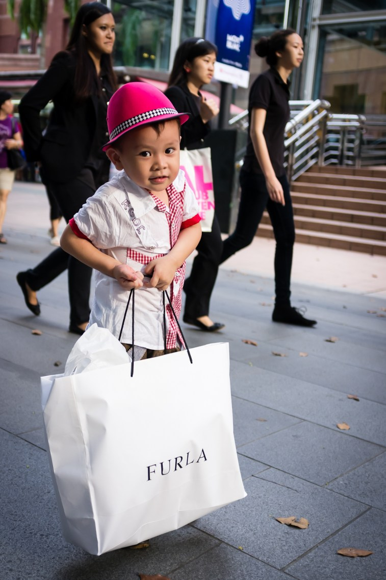 Street photography - Little boy with a pink hat helping to carry shopping bags