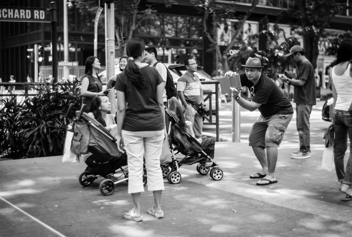 Street photography - Tourist taking photos with a tablet