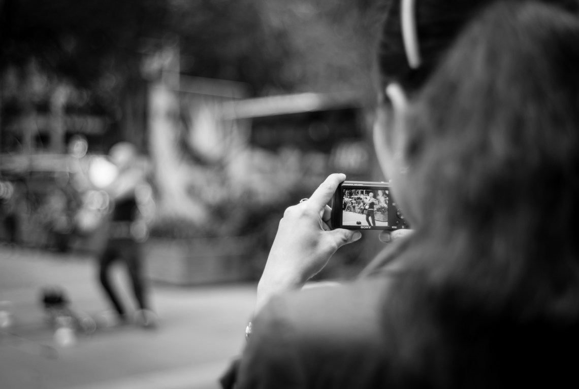 Street photography - Woman recording a video of a street performer